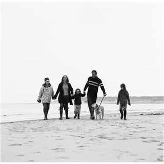 Family walking with dog on beach