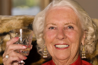 Older woman celebrating with wine